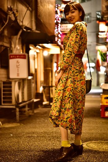 Full length of woman standing on street at night