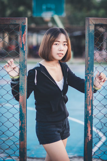 One Person Real People Three Quarter Length Focus On Foreground Leisure Activity Lifestyles Fence Portrait Looking At Camera Standing Day Young Women Casual Clothing Child Boundary Young Adult Women Barrier Hairstyle Bangs Beautiful Woman Innocence