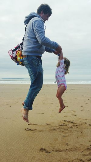 Full Length Sand Beach Jumping Mid-air Child Casual Clothing Sea People Childhood Outdoors Sky Natural Parenting Fun Father And Daughter Childhood Memories