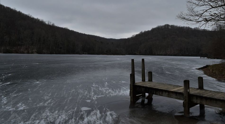 Pier on lake against sky during winter