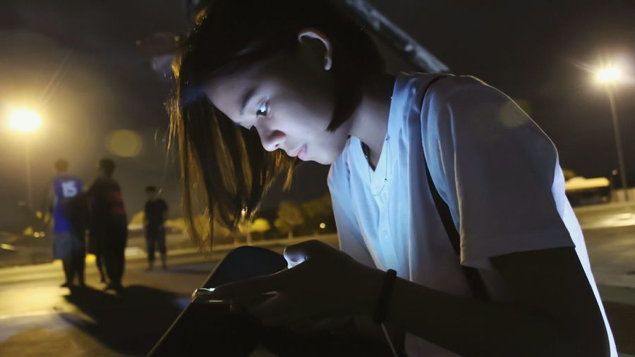 Woman using smart phone against illuminated city street at night