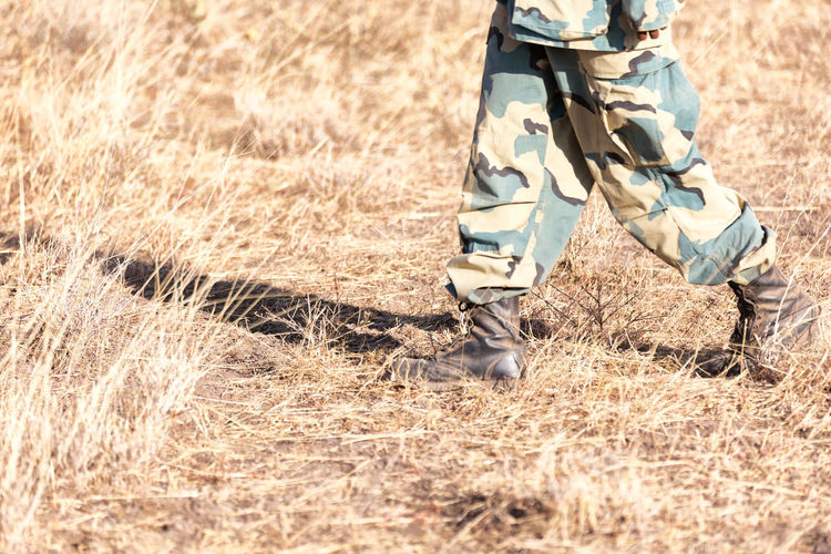 Low section of soldier walking on field
