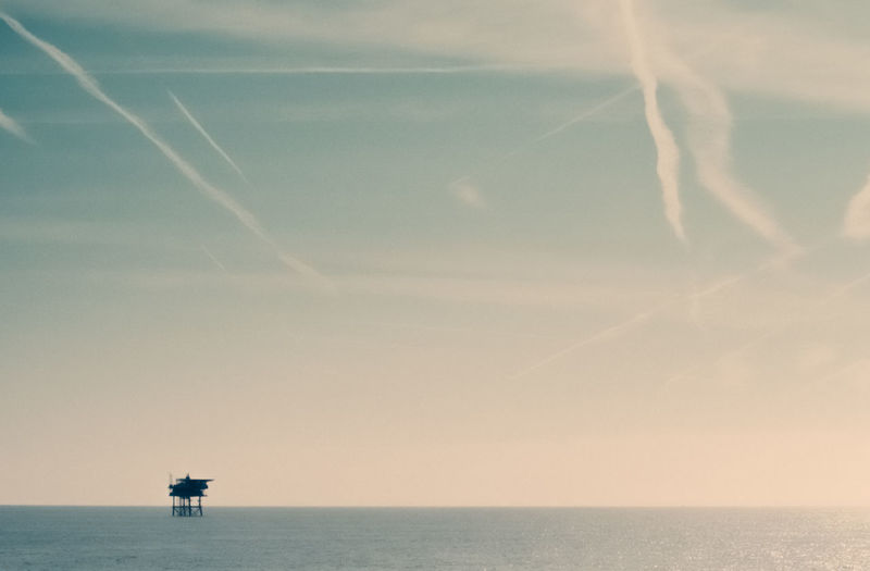 Scenic view of sea against vapor trails in sky