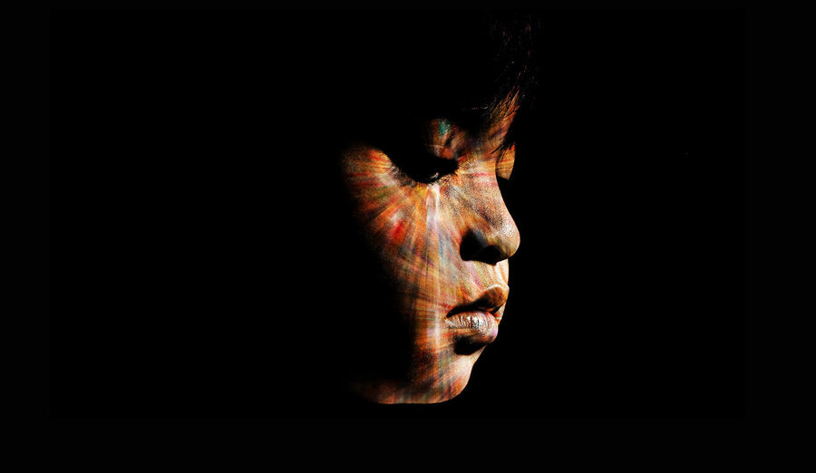 Close-up of boy face against black background