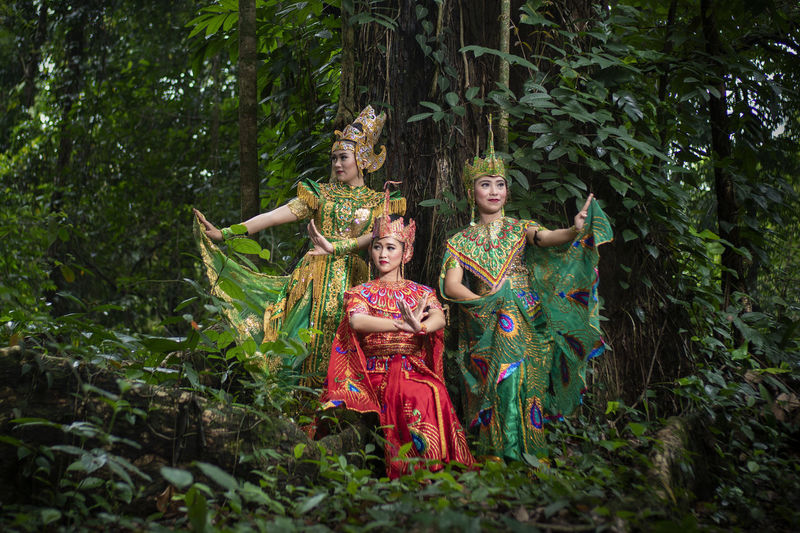 Friends wearing traditional clothing standing amidst plants in forest