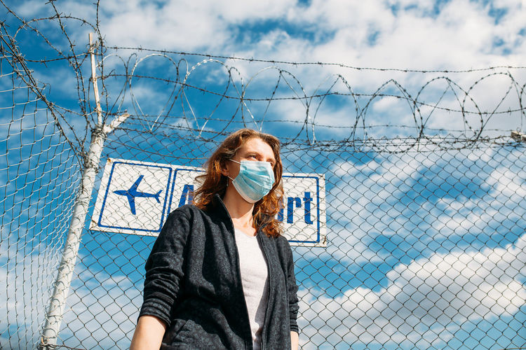 Portrait of woman standing by chainlink fence against sky