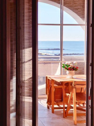 Chairs and table by sea seen through window