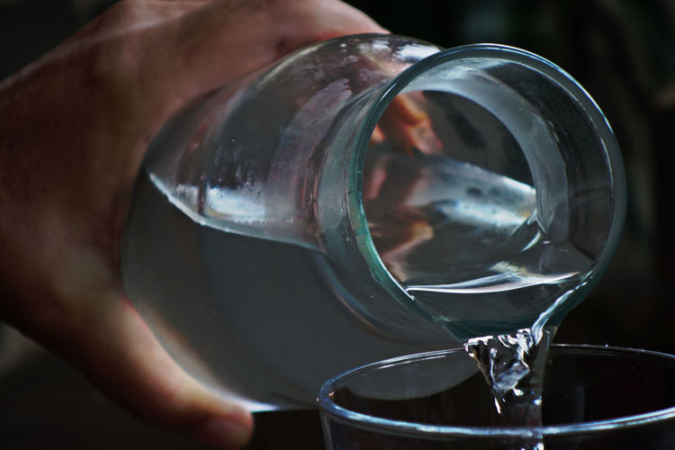 Cropped Image Of Person Pouring Water In Drinking Glass