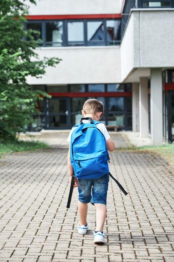 Rear view of boy walking on street against building