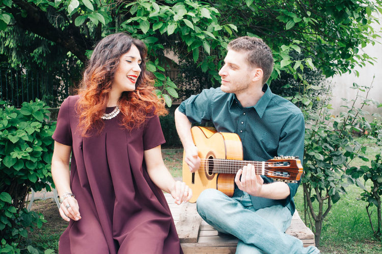 Young couple playing guitar in park