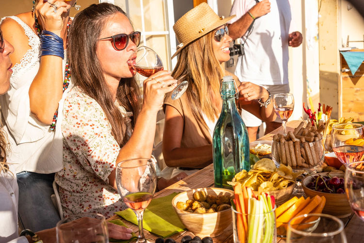 Female friends enjoying food and drink during party at building terrace