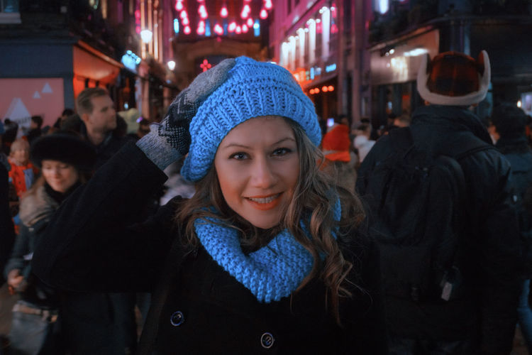 Portrait Of Smiling Woman Wearing Warm Clothing And Knit Hat At Night