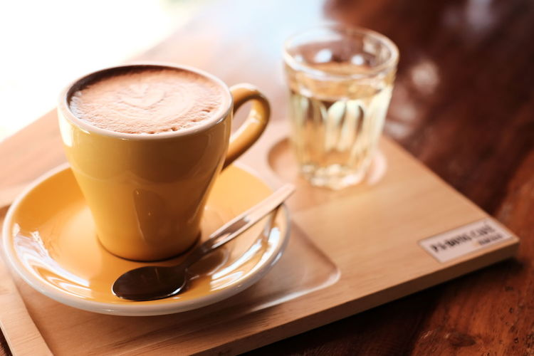 Yellow cup of Hot coffee in break time at cafe , film look effect image tone. Table Food And Drink Drink Coffee - Drink Refreshment Coffee Coffee Cup Mug Cup Latte Cafe Coffee Shop Hot Drink Frothy Drink Coffee Shop Cappuccino
