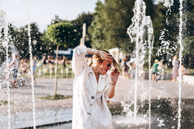 Young Woman Enjoying At Water Fountain
