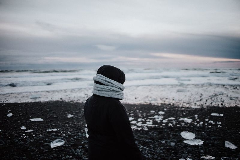 Man Looking At Frozen Sea While Standing Against Cloudy Sky During Sunset