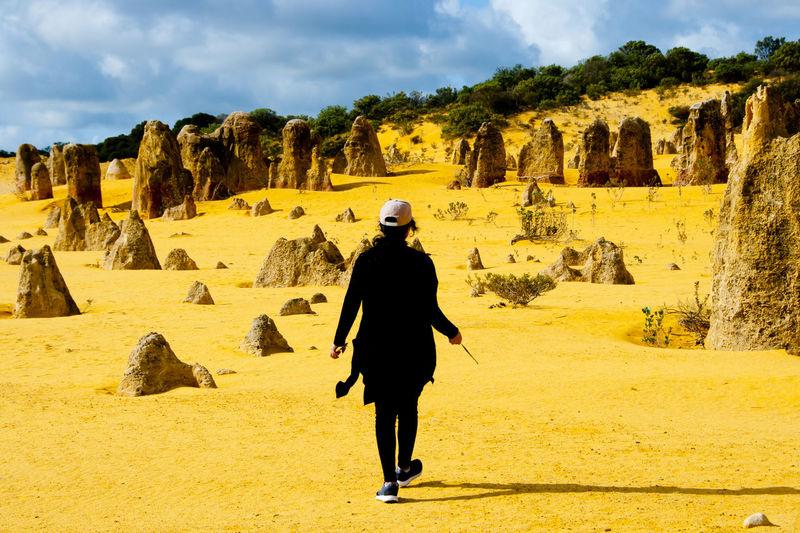 Full length rear view of woman walking in desert