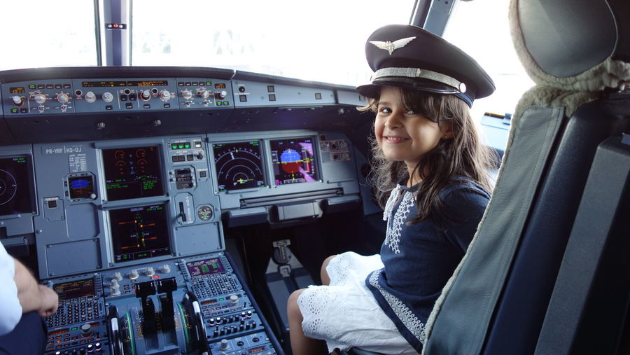 child flight attendant Child Cockpit Airplane Piloting Pilot Control Panel Sitting Smiling Air Vehicle Journey Technology