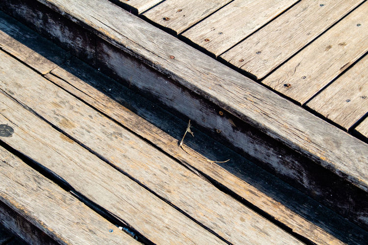 High angle view of wooden bench on boardwalk