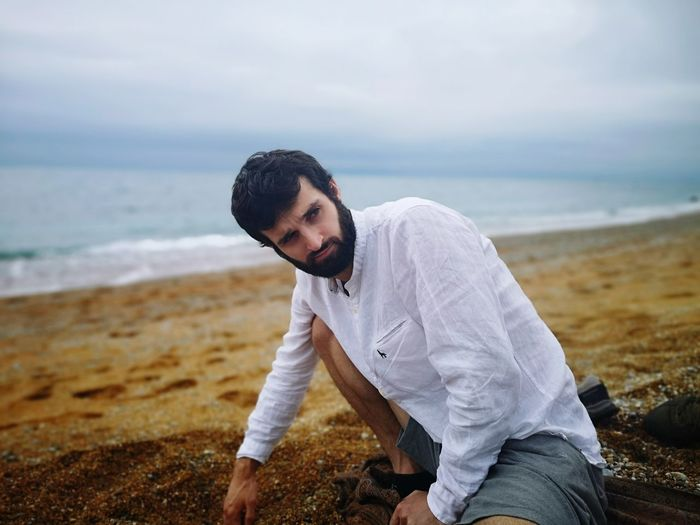Bearded young man sitting at beach against cloudy sky