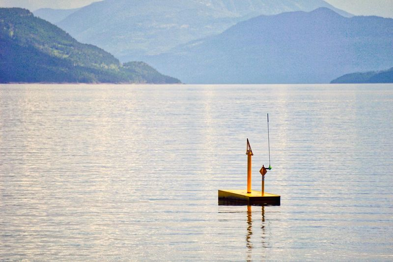 Yellow buoy on calm blue waters Beauty In Nature Blue Buoy Calmness Complementary Colors Day Lake Misty Morning Mountain Nature Nautical Vessel Outdoors Reflection Scenics Tranquility Water Yellow