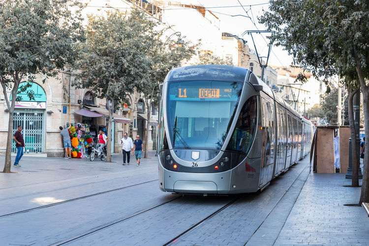 Jerusalem, Israel, 28, September, 2018 : Jerusalem city tram rides on one of the central streets of the city in Jerusalem Lifestyle Road Architecture City Electric Jerusalem Israel Public Transportation Traffic Transportation Building Cable Capital Central Street City Tram Culture District Famous Place Landmark Location Symbol Tourism Town Tramway Travel Destinations Urban