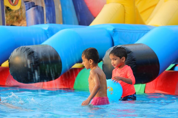Boys playing in swimming pool at resort