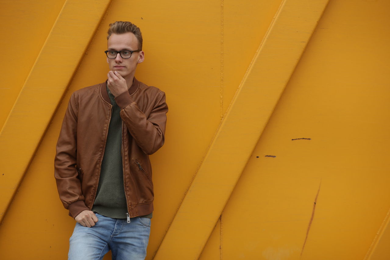 Adult Adults Only Casual Clothing Day Eyeglasses  Fashion Hands In Pockets Jacket Lifestyles One Man Only One Person Outdoors People Portrait Scarf Standing Three Quarter Length Yellow Yellow Background Young Adult