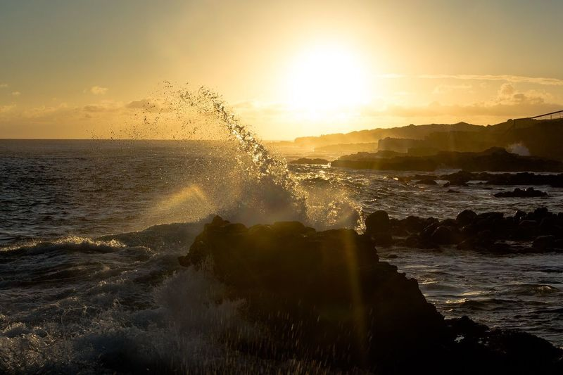 Water Splashing In Sea Against Sky During Sunset