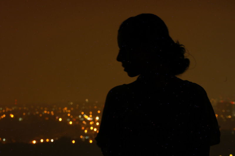 Silhouette woman standing against sky at night
