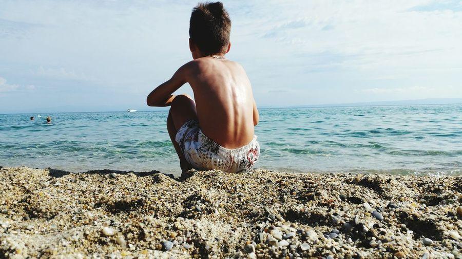 Shirtless boy sitting at beach against sky