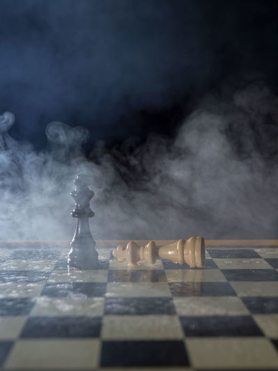 white and black kings on a chessboard at the end of the battle, with smoke and fog. win and lose concept SURRENDER Arts Culture And Entertainment Black Background Board Game Checked Pattern Chess Chess Board Chess Piece Game Indoors  King - Chess Piece Knight - Chess Piece Leisure Activity Leisure Games No People Relaxation Selective Focus Smoke - Physical Structure Still Life Strategy