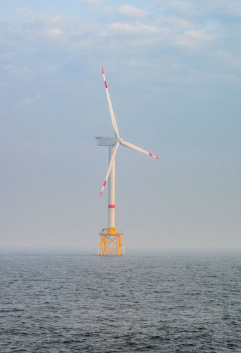 Wind turbine in sea against sky