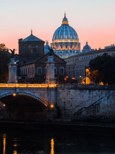Illuminated buildings against sky during sunset in city, rome