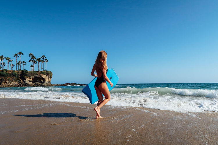 Young beautiful girl with surfboard on the ocean beach Beach Beauty In Nature Bikini Blue Body & Fitness Clear Sky Day Extreme Holiday Nature Outdoors Pacific Ocean Sand Sea Summer Surf Surfboard Surfing Tropical Vacation Vacations Water
