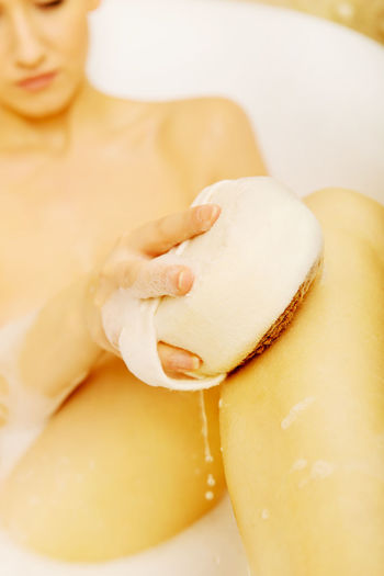 Midsection Of Sensuous Woman Taking Bath In Bathtub