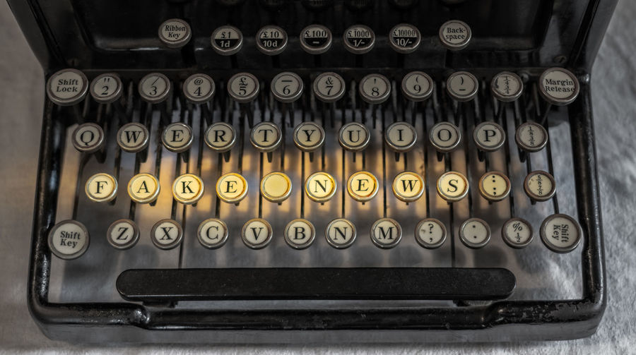Fake News spelled out on the keys of an old antique typewriter as concept for modern journalism Journalist Negative Newspapers Politics Reporting Truth Communication Fake News False Journalism Letter Lie Lies Media Message No People Old Reporter Story Text Typewriter