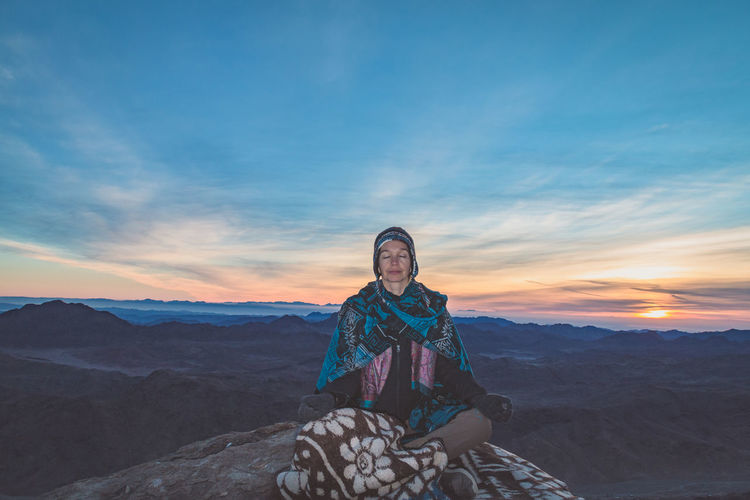 Woman meditating while sitting on rock against sky during sunset