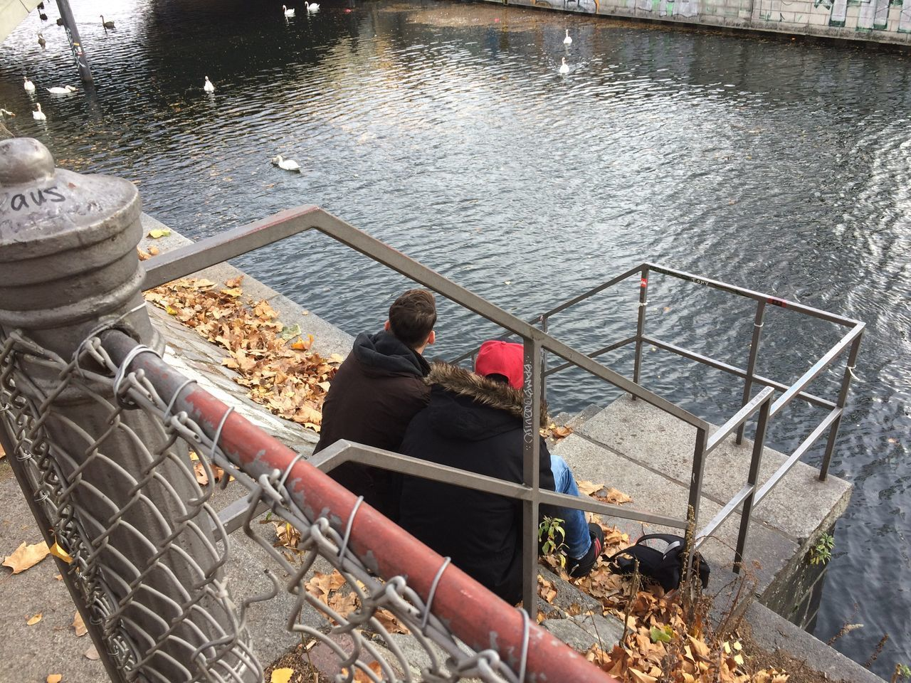 High Angle View Of Men Sitting By Canal