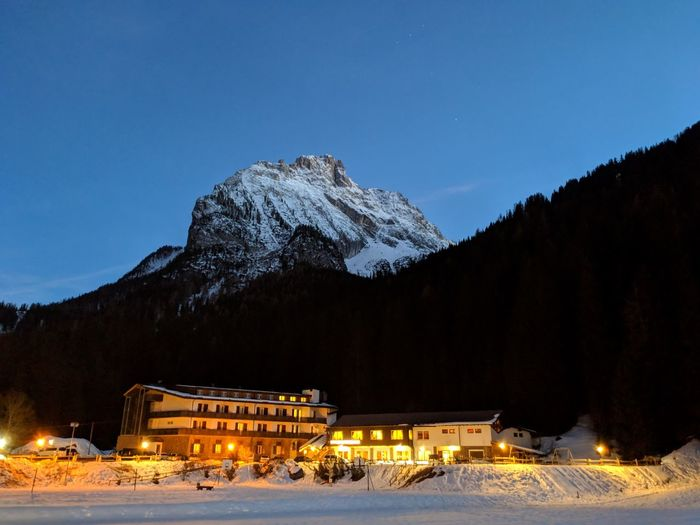 Illuminated building against snowcapped mountains at night