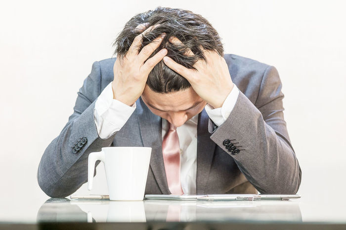 Adult Business Business Person Businessman Day Depression - Sadness Disappointment Head In Hands Men Occupation One Man Only One Person People Sitting Suit Tensed Well-dressed White Background Working Worried