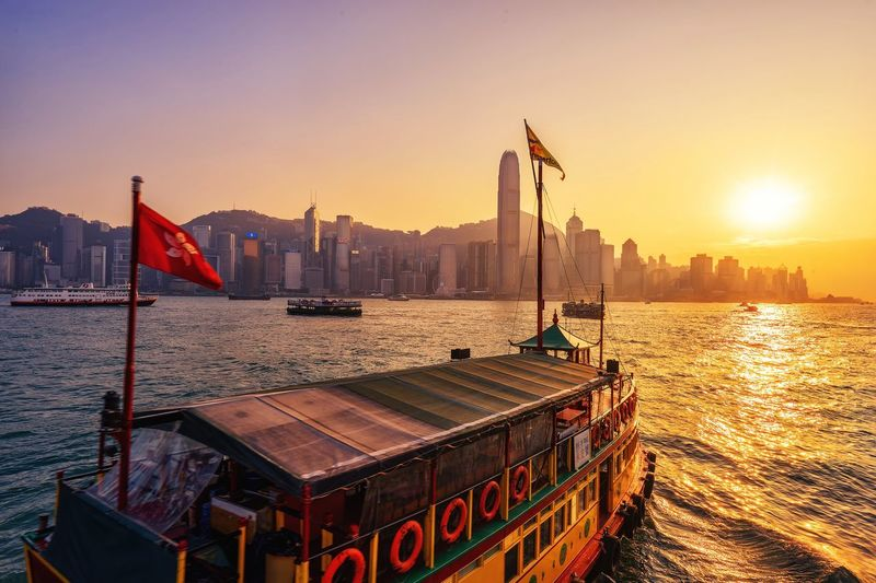 sailing Flag Sunset Patriotism Water Built Structure Architecture Sun Sea Transportation Sunlight Travel Sky No People Mountain Building Exterior Nautical Vessel Outdoors Waterfront City Travel Destinations The Week On EyeEm City HongKong EyeEmNewHere Transportation The Week On EyeEm