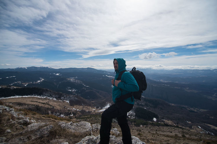 Side view of man with backpack standing on mountain against cloudy sky