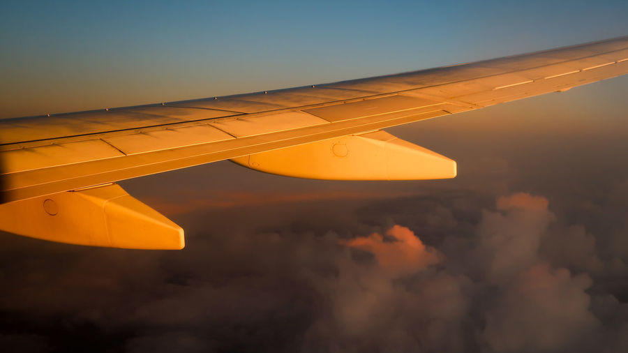 Airplane wing during sunset with cloudscape