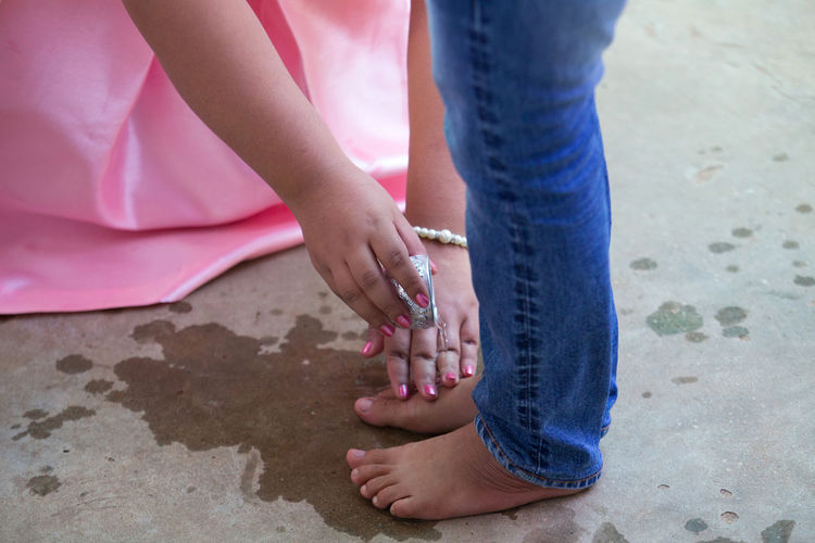 Person washing woman feet on ground