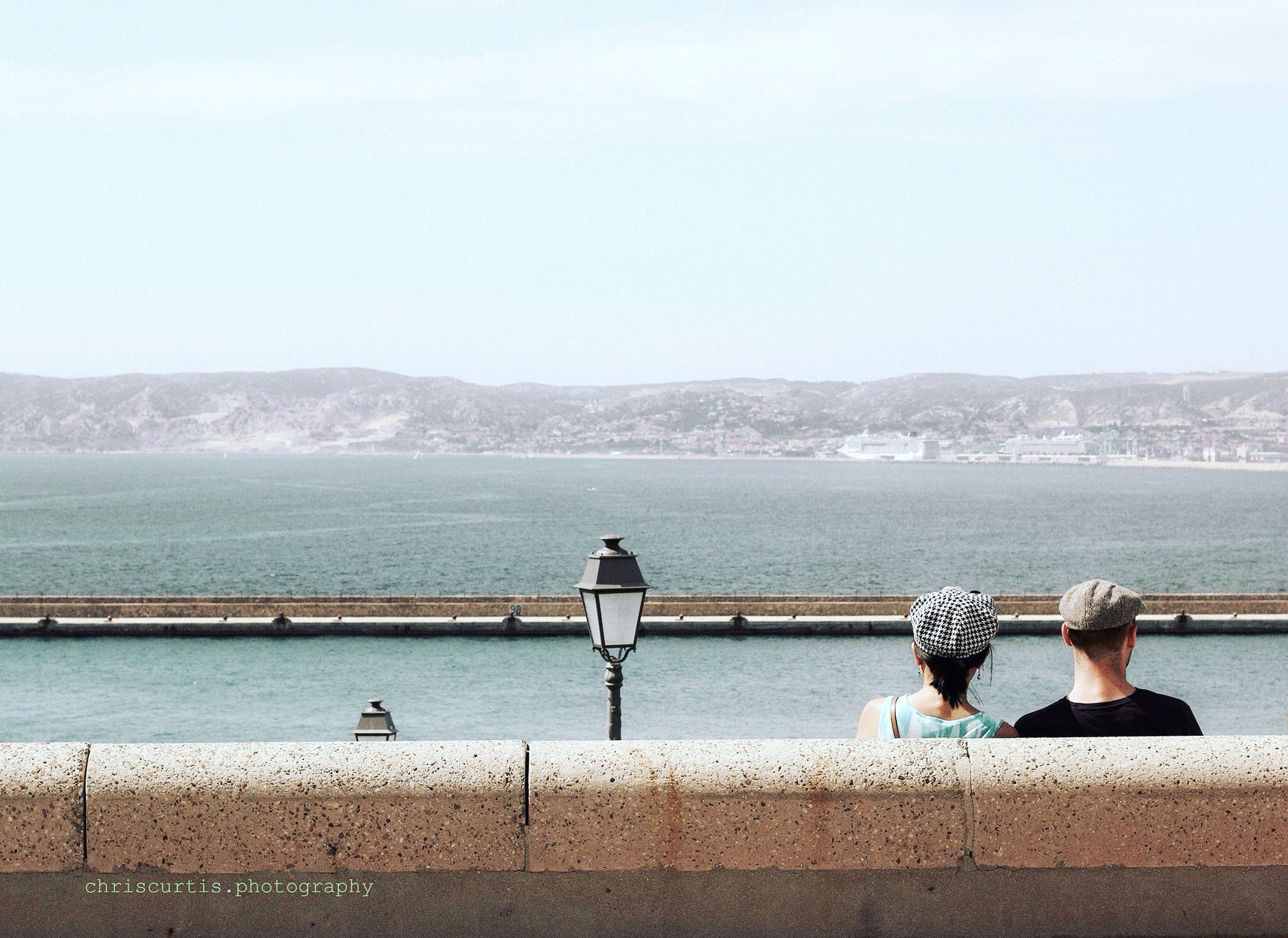 REAR VIEW OF PEOPLE STANDING ON RAILING AGAINST SEA
