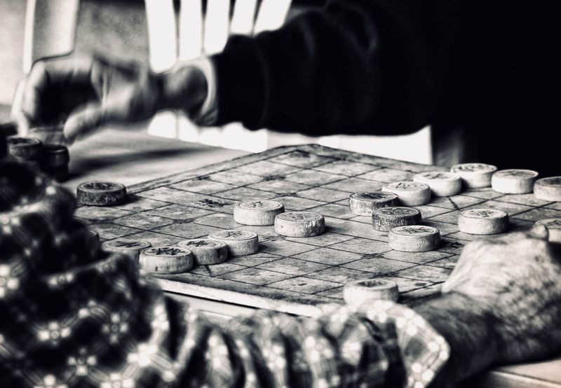 Old times Streetphotography Blackandwhite Focus Movement Past Time China Guangzhou Chinese Chess Board Games One Person Selective Focus Real People Table Indoors  Human Hand Men