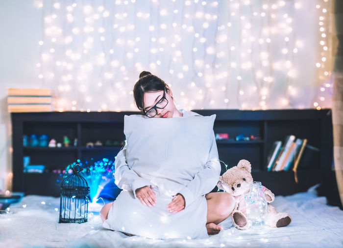 Young Woman Embracing Pillow While Sitting Amidst Christmas Lights On Bed