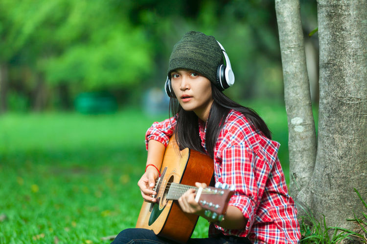 Portrait Of Woman Playing Guitar On Field