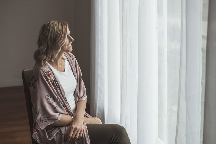 Woman looking through window at home