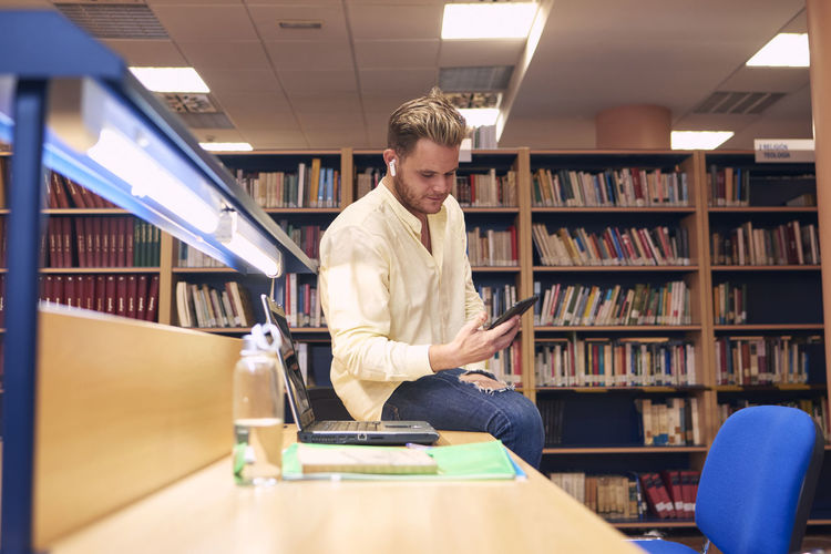 Portrait of a boy making a video call in a library